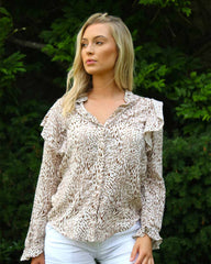 Woman in frilled button down blouse with beige small tiger print. She is outside and wearing white shorts.