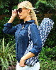 Woman smiling with navy shirt with blue ikat charity yoga bag on her shoulder.