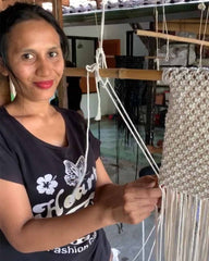 Woman making woven square charity bag from scratch at a charity.