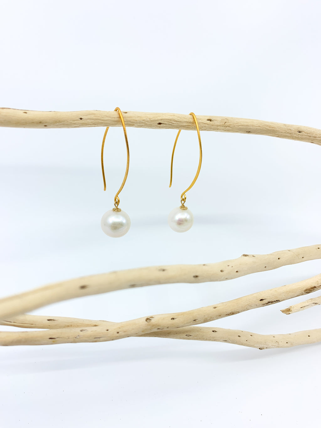 white pearl earrings with long mat gold hook by eve black jewelry made in Hawaii