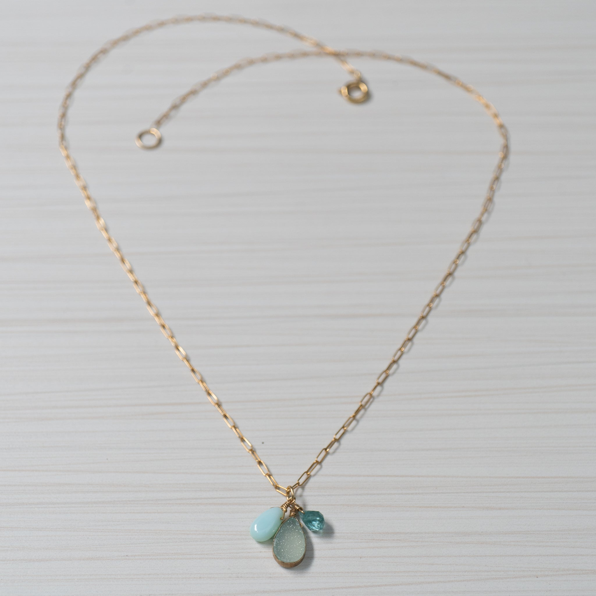 blue gemstones on simple gold necklace handmade in Hawaii by eve black jewelry  Edit alt text