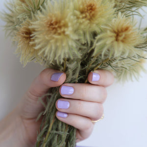 A female holding a bunch of flowers, wearing Lilac Fizz a purple shade of nail polish