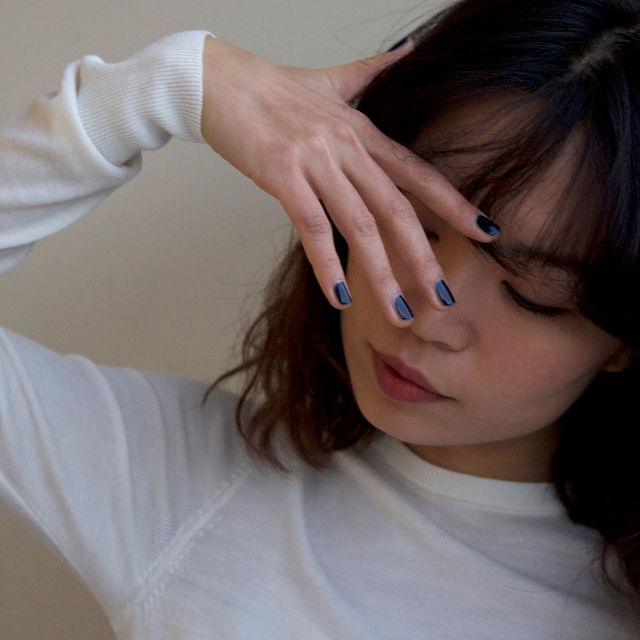 A female with her hand across her face wearing Midnight Sky, a dark blue nail polish.