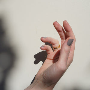 A female hand against a light backdrop in the sunlight, wearing Wet Cement a light grey nail polish and one gold ring