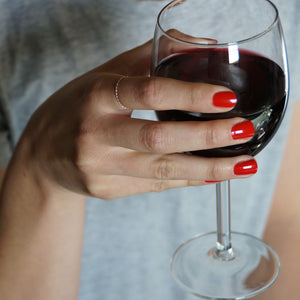 A female hand holding a glass of red wine, wearing Paint Red nail polish, a classic bold red shade