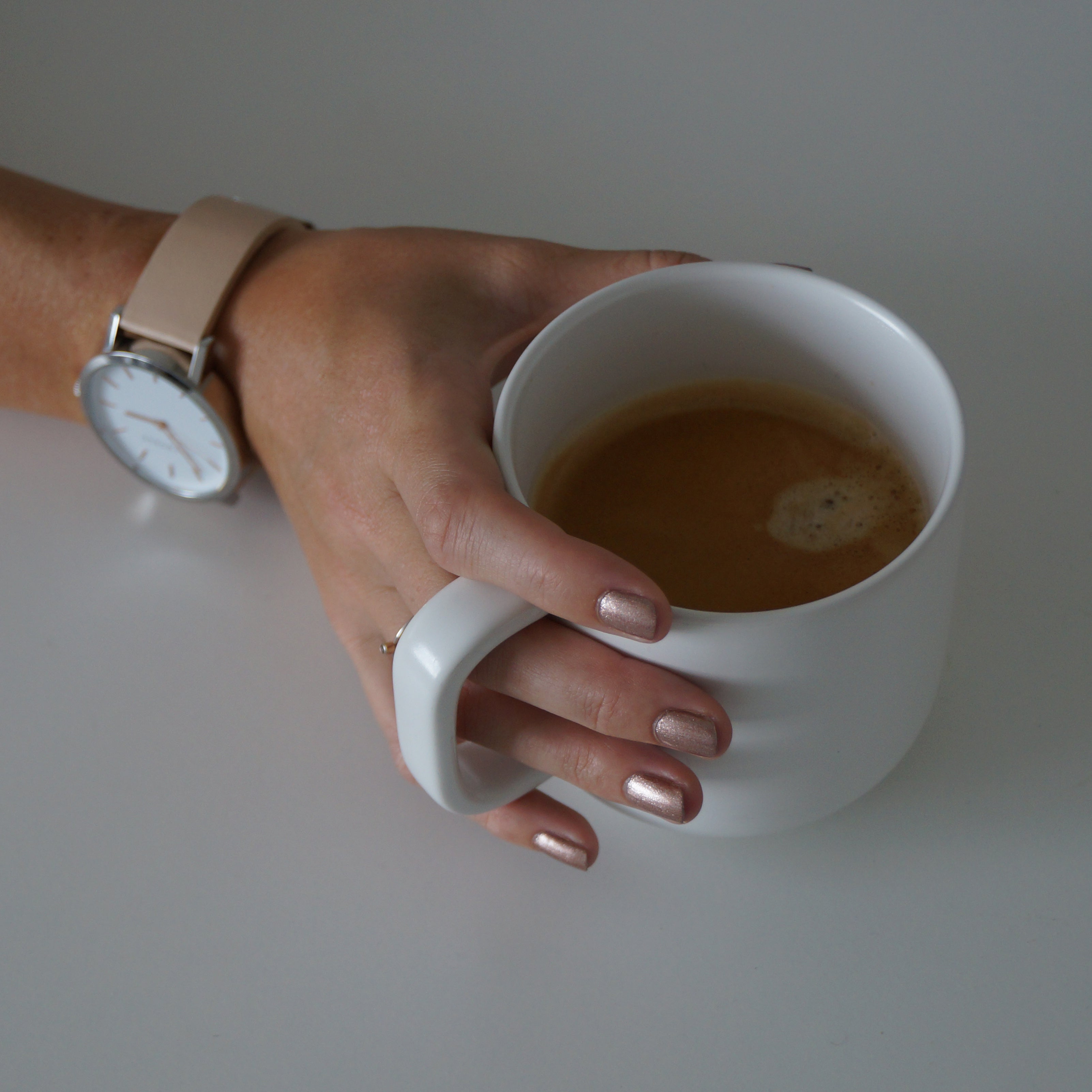 A female hand holding a cup of coffee, wearing Copper Blush nail poilsh - a metallic dark pink colour with gold undertones