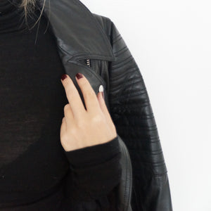 A female grasping her black leather jacket, wearing Lady Voodoo a dark red nail polish
