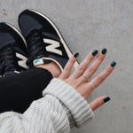 A female holding out her hand, wearing Sea Queen, a dark green nail polish. Contrasting against her black jeansm New Balance shoes, and light grey concrete in the background.