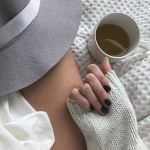 A female clutching a hand on the sleeve of her white woolen sweater, wearing Storm Grey, a dark blue gey colour of nail polish by Paint Nail Lacquer.