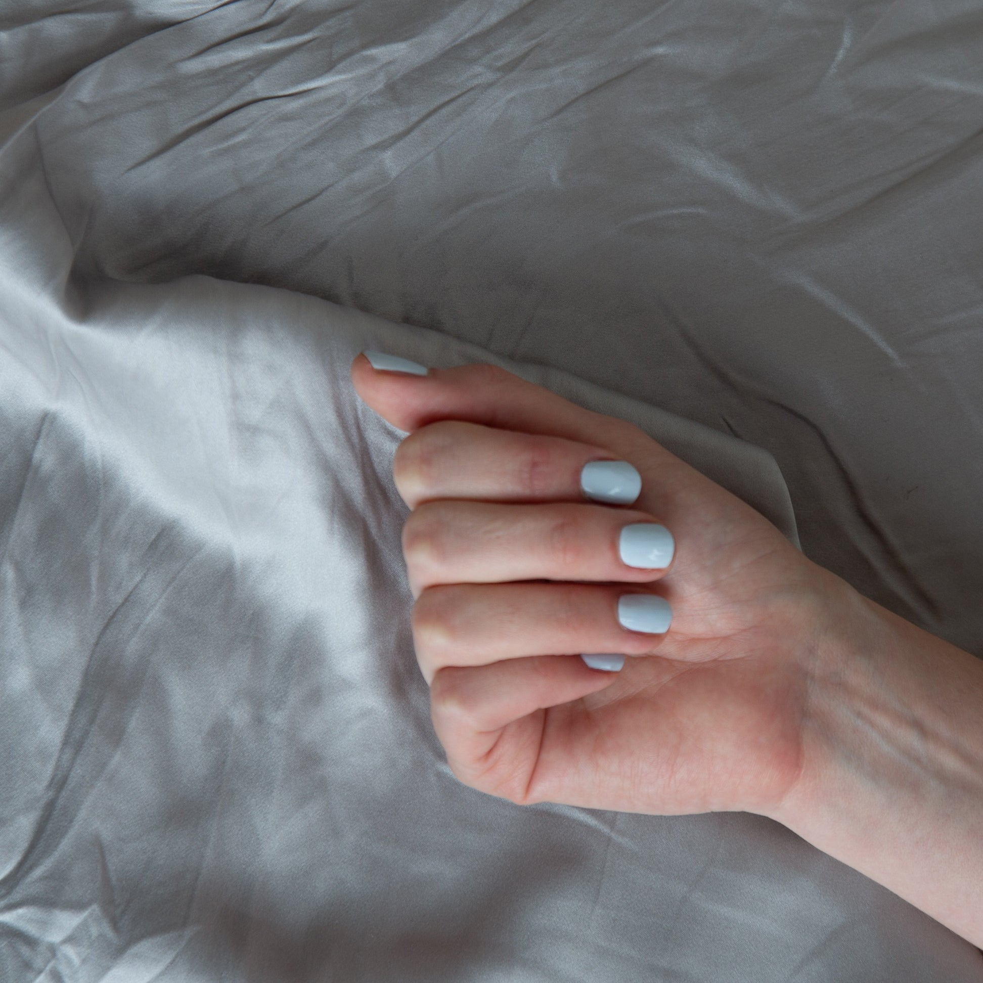 A female clutching her hand against a grey backdrop, wearing Pale Glacier, a light baby blue colour of nail polish
