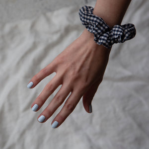 A female hand streched out against a grey backdrop, wearing Pale Glacier a baby blue nail polish and a black and white gingham scrunchie on her wrist