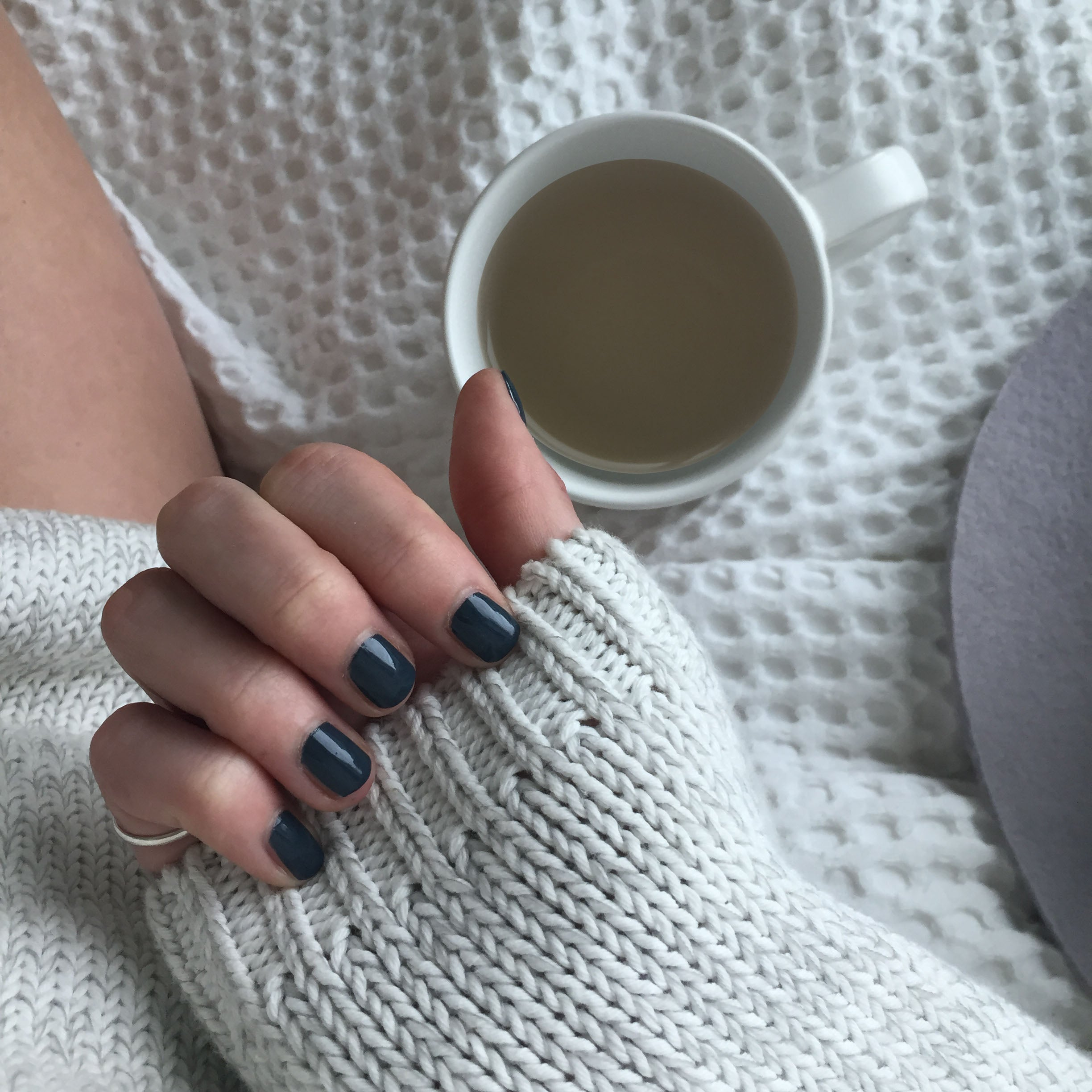 A female clutching the sleeve of her white woolen sweater wearing Storm Grey, a dark blue grey nail polish with green undertones. Constrasting to her cup of tea and blanket in the background.