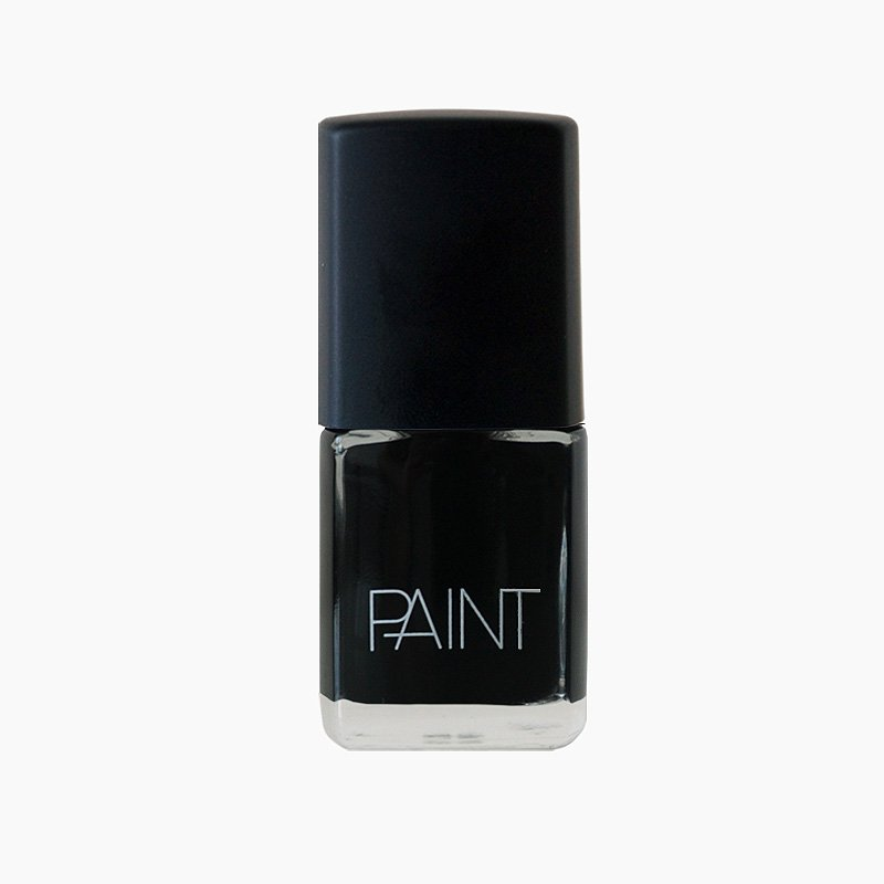 A bottle of Black Dog nail polish by Paint Nail Lacquer against a white backdrop, this shade is a classic midnight black colour
