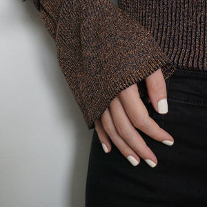 A female hand on hip wearing Coconut Cream paint nail polish a creamy white gloss shade
