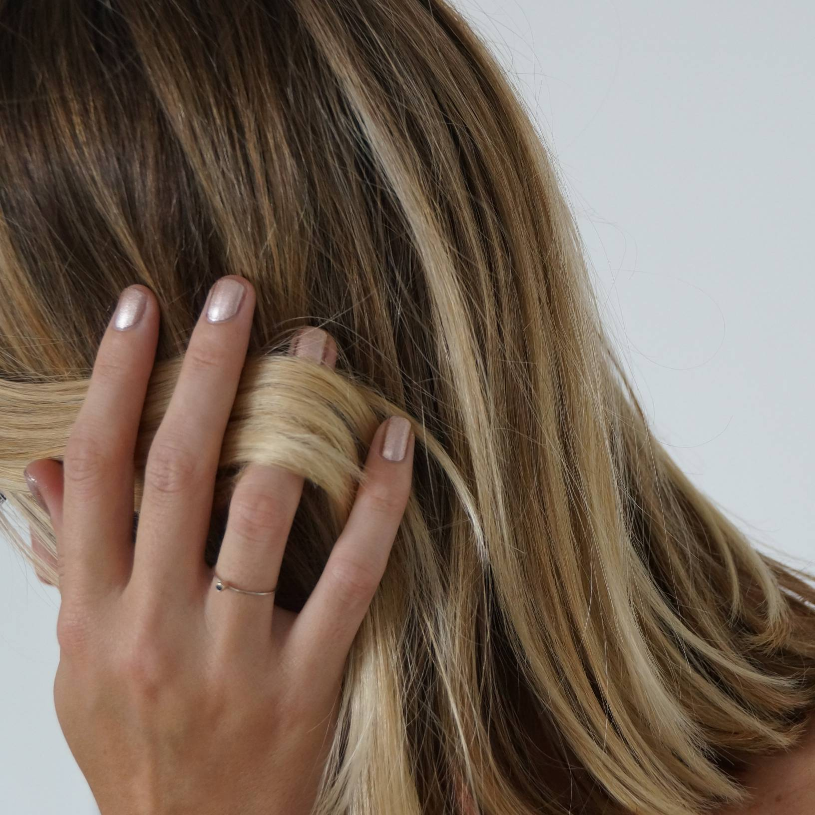 A female side on view holding a lock of hair whilst wearing Copper Blush nail polish, a metallic dark pink shade with gold undertones