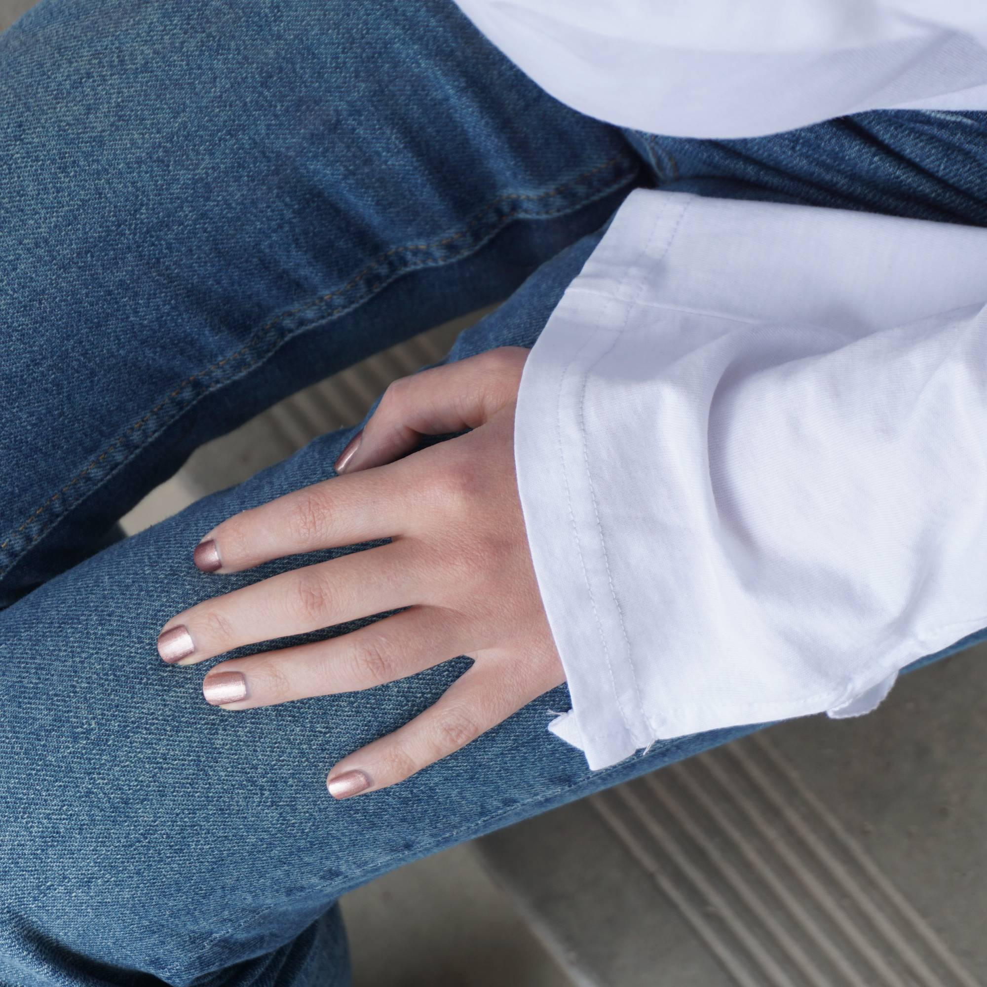 A female resting her hand on blue denim jeans wearing Galatic Rose nail polish a metallic dark bronze with pink undertones