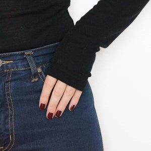 A female with her hand resting on her blue denim jeans wearing Lady Voodoo nail poish, a dark red shade with black and gold undertones.