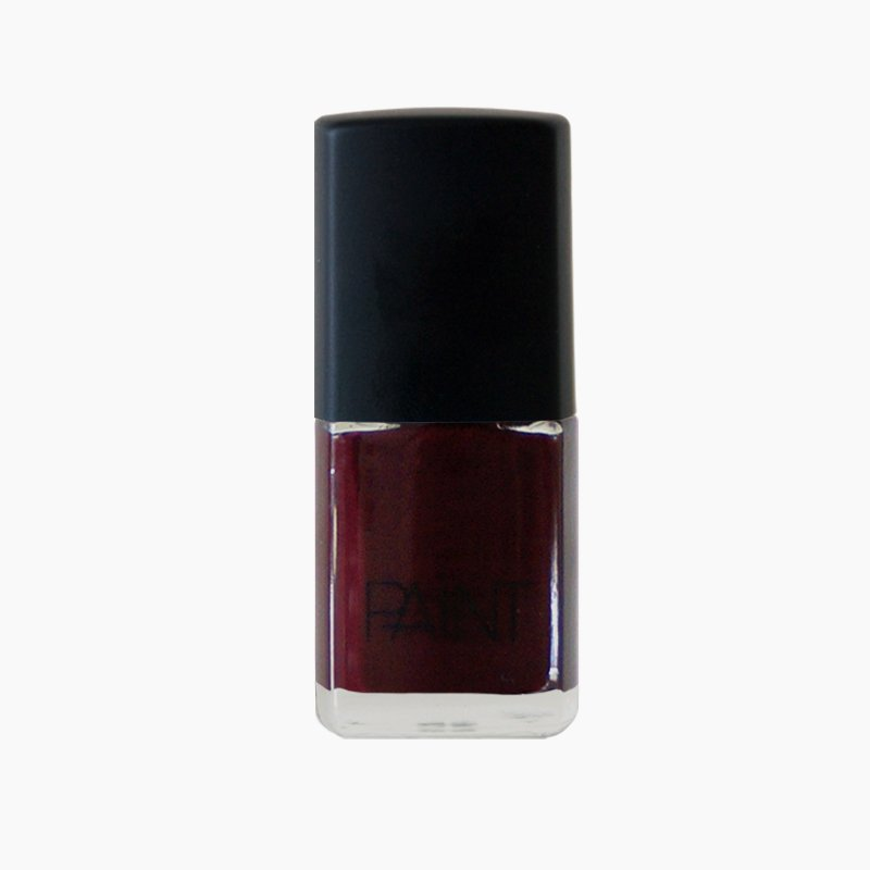 A bottle of lady voodoo nail polish by Paint Nail Lacquer against a white backdrop, this shade is a dark red with black and gold undertones