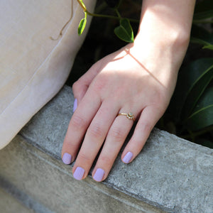 A female resting her hand on concrete, wearing Lilac Fizz a light purple shade of nail polish