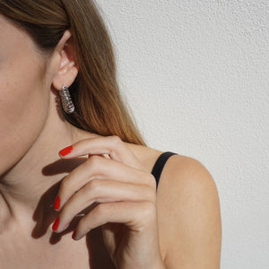 A female reaching for her silver earring whilst wearing Paint Red nail polish, a classic red shade.