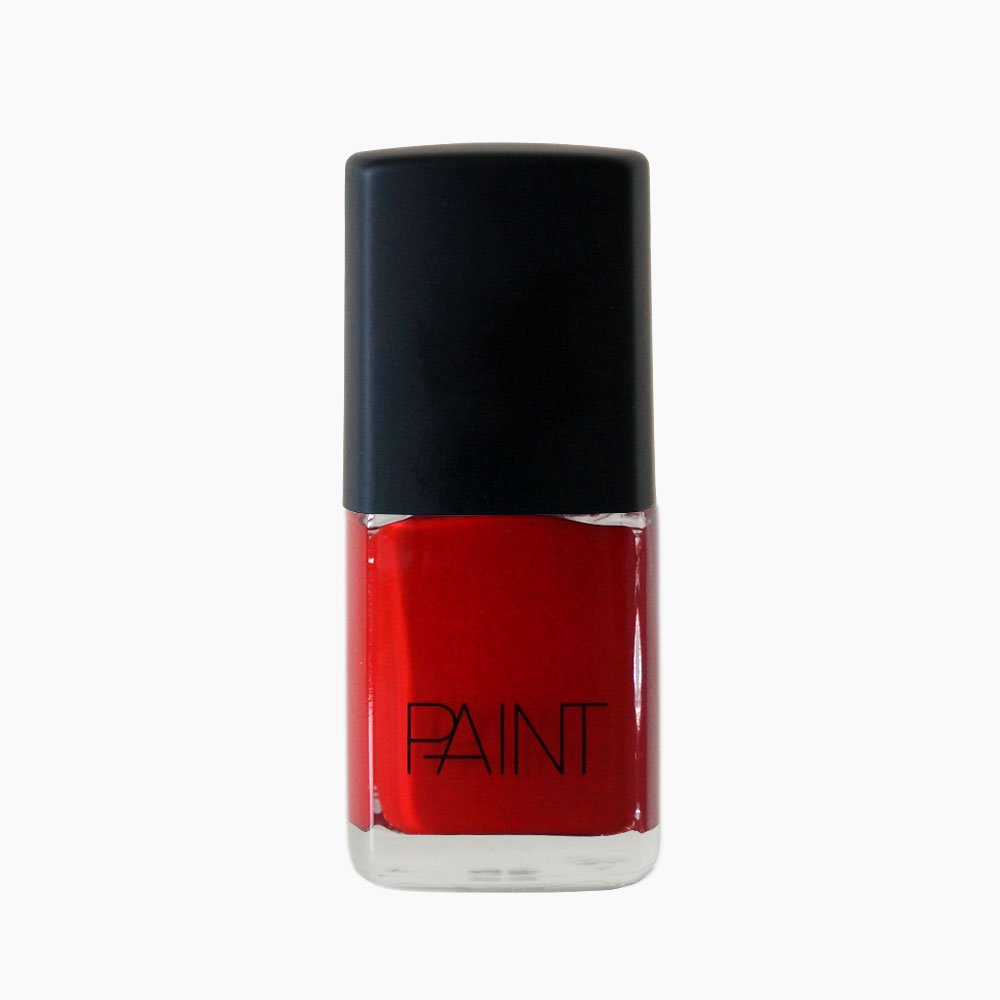 A bottle of Paint red nail polish by Paint Nail Lacquer against a white backdrop, this shade is a classic red