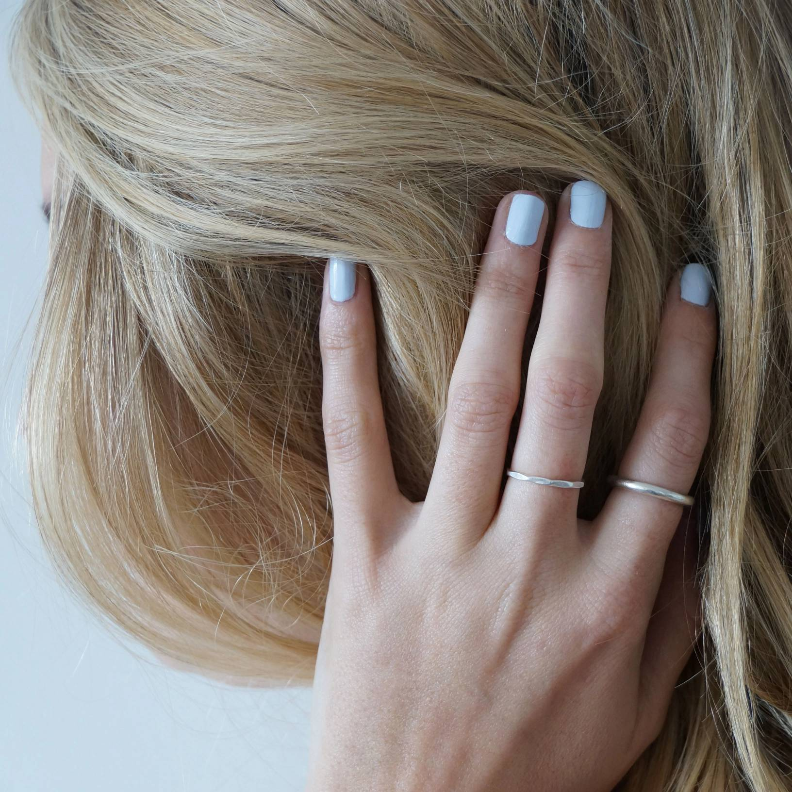 A female with her hand clutching her hair wearing Pale Glacier a light baby blue colour by Paint Nail Lacquer