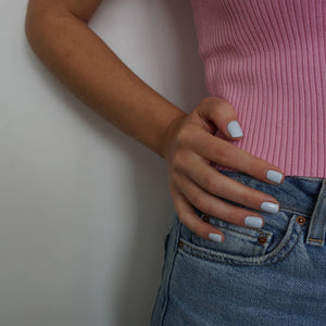 A female hand on hip, wearing Pale Glacier a baby blue nail polish, contrasting against her pink top and denim skirt.