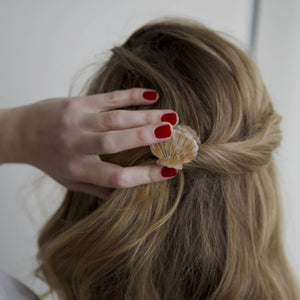 A female clutching the back of her hairclip, wearing Scarlet Venom a dark red nail polish by Paint Nail Lacquer