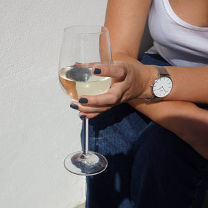 A female holding a glass of white wine in the sunlight, wearing Storm Grey nail polish, a dark blue grey shade.