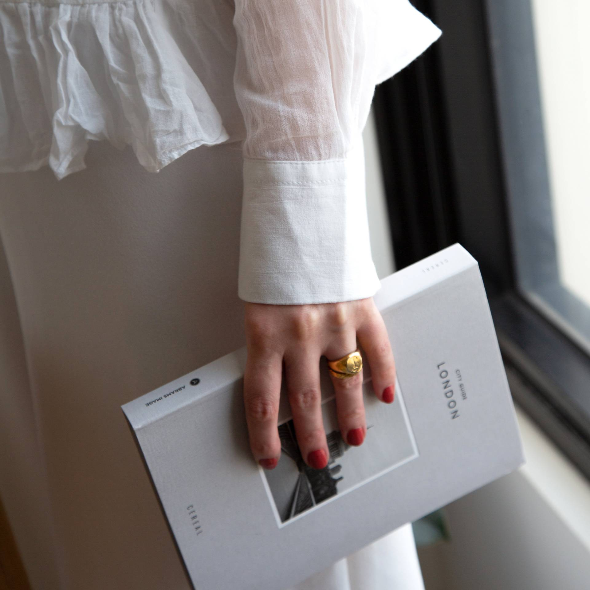A female holding a white book about London, wearing Tuscan Summer a burnt orange shade of nail polish and a gold ring.