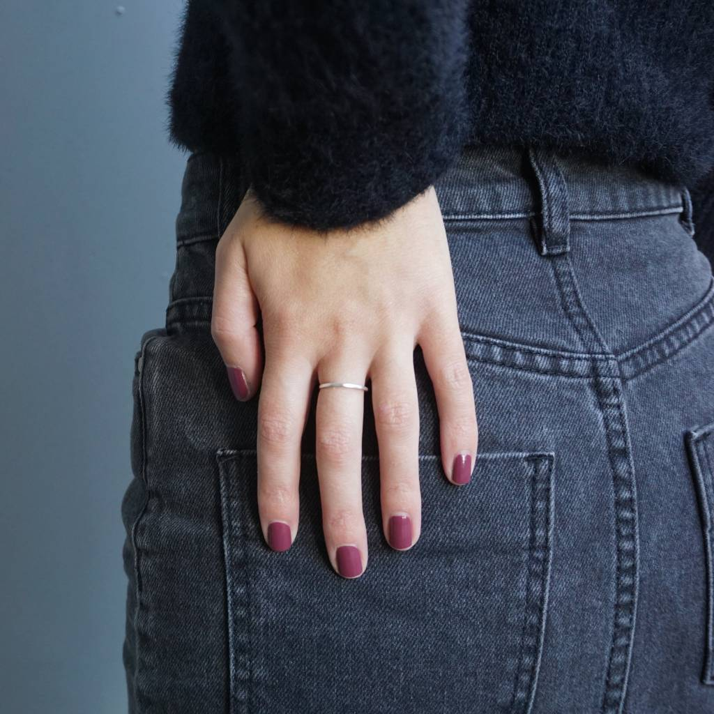 A female's hand resting on her backside wearing Velvet Berry nail polish, a dark pink shade. Contrasting against her faded black denim jeans.