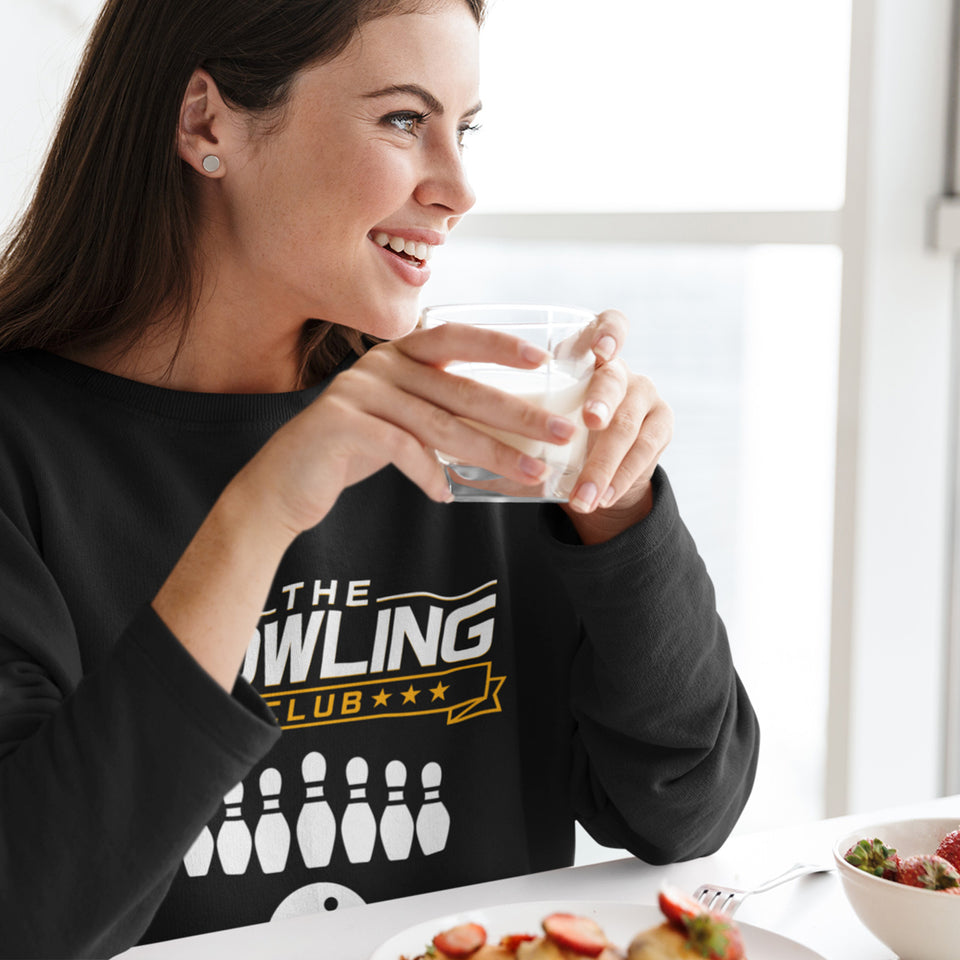 "A woman eating breakfast in a ""The Bowling Club"" t-shirt"