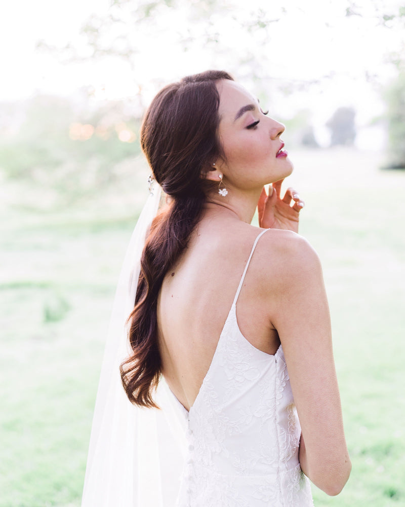 Model wearing Belle Fleur Earrings by Atelier Elise with long and airy tulle veil