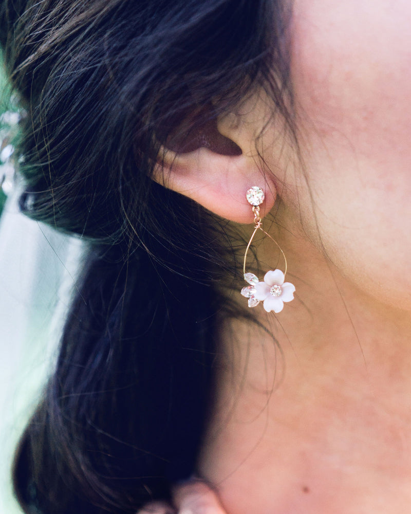 Close up on model of the Belle Fleur Earrings by Atelier Elise in rose gold with blush flowers and crystals.