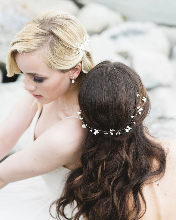 delicate Bell Fleur Hair Vine made of dainty flowers, freshwater pearls, and Swarovski crystals; styled to the back half up braid with flowing waves