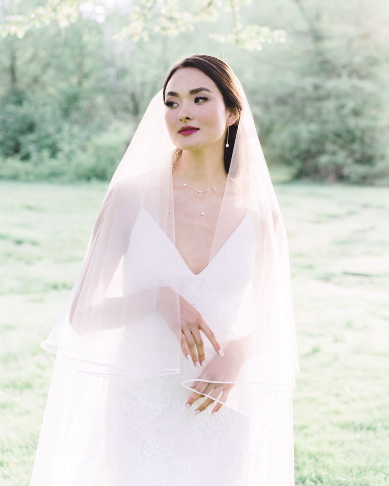 Model wearing calla long wedding veil with blusher