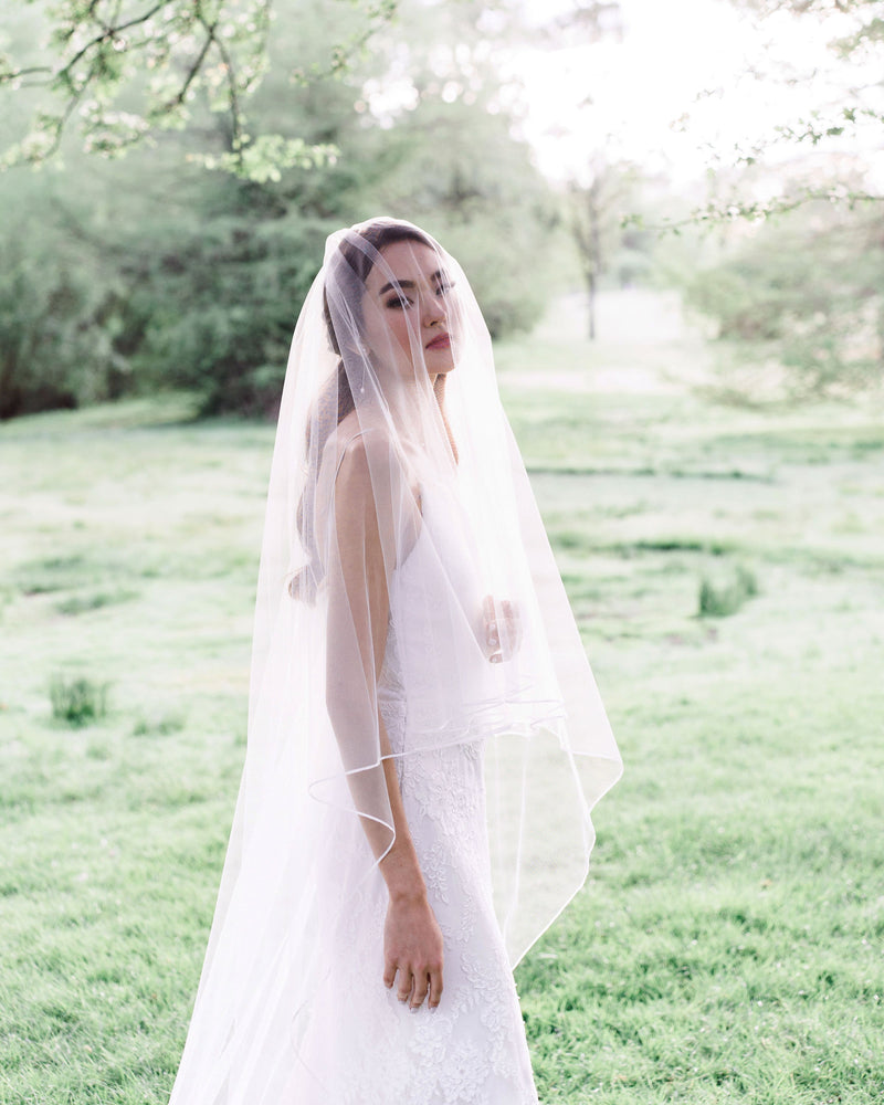 shot with veil model wearing calla bridal veil with ribbon edge and blusher