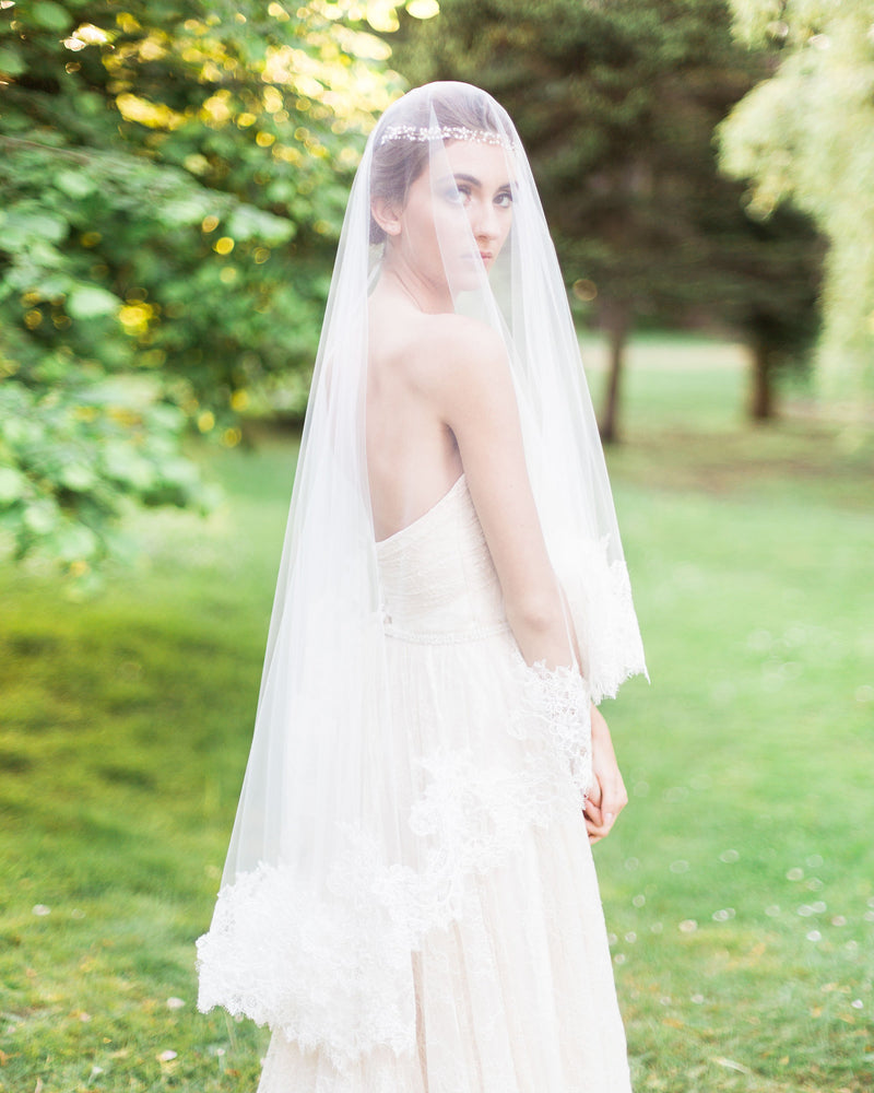 model wears cassia chantilly lace fingertip wedding veil with  blusher