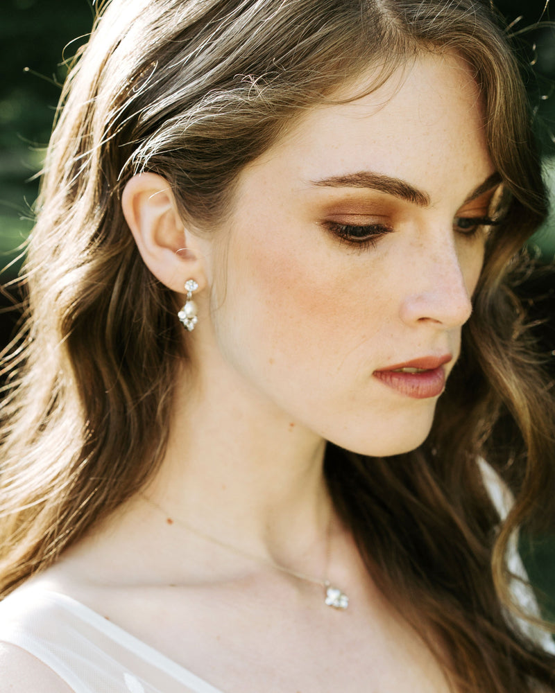 model wearing celestial silver pearl drop earrings in silver with cream freshwater  pearl and swarovski crystals bridal jewelry