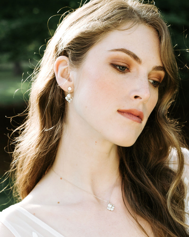 model wearing celestial drop necklace in gold with natural freshwater pearl and swarovski crystals bridal jewelry set