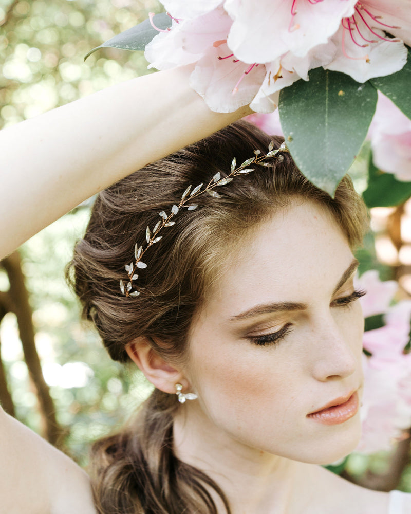model wearing swarovski crystal leaf earrings in gold with leaf hair vine