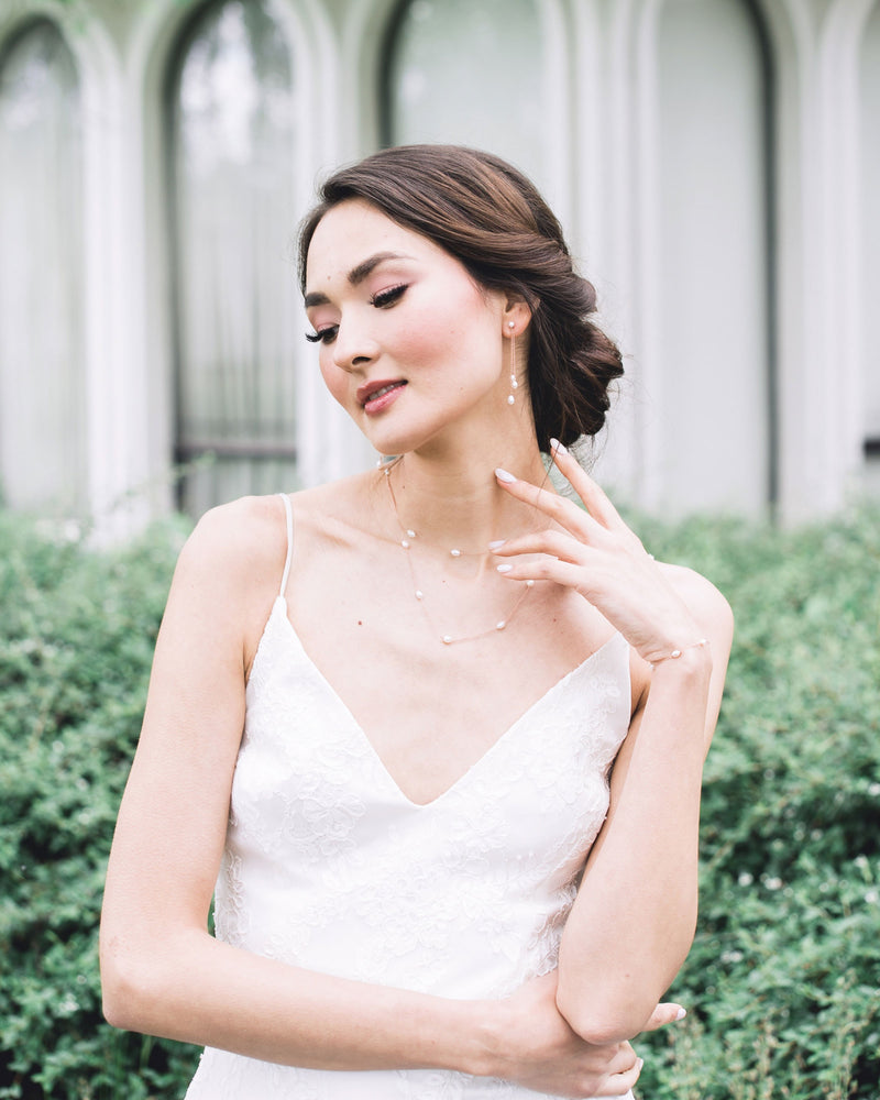 model wearing the dainty pearl layered necklace in rose gold, paired with the matching dainty pearl bracelet and dainty pearl trio earrings.