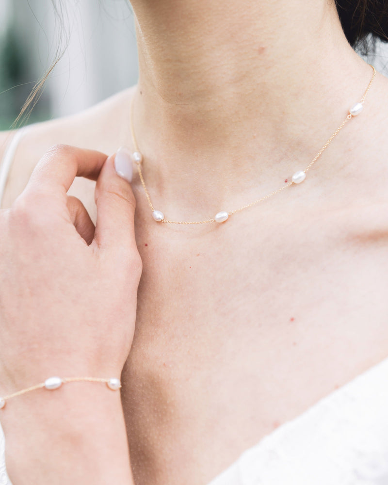 Close-up of the Dainty Pearl Necklace in gold on a model, paired with the Dainty Pearl Bracelet.
