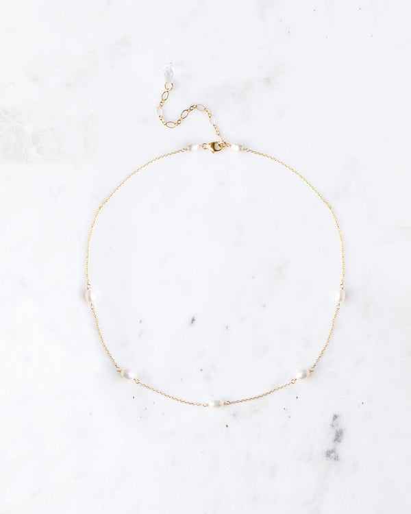 Flatlay of the Dainty Pearl Necklace in gold, with five scattered freshwater pearls on delicate chain