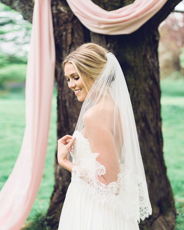 Model wearing playful waist veil with intricate Chantilly lace