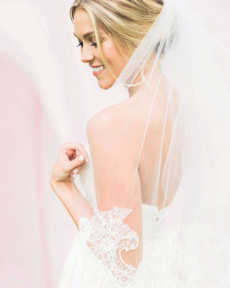 Model wearing playful wedding veil with intricate Chantilly lace