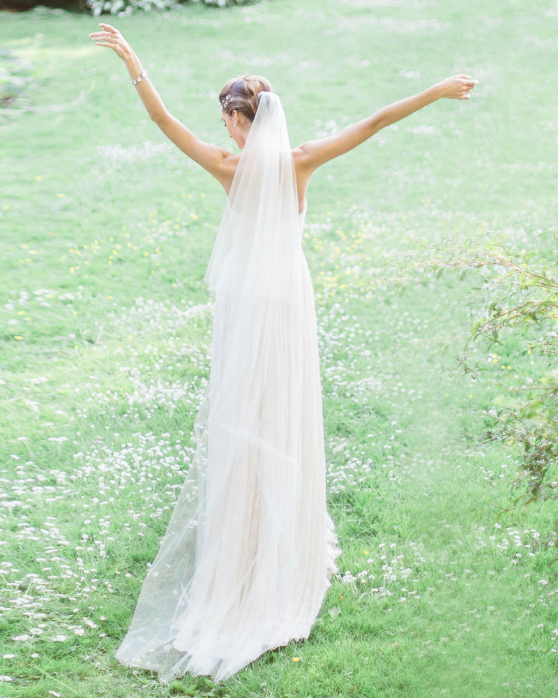 Model wearing circular cut illusion tulle chapel wedding veil without gathers