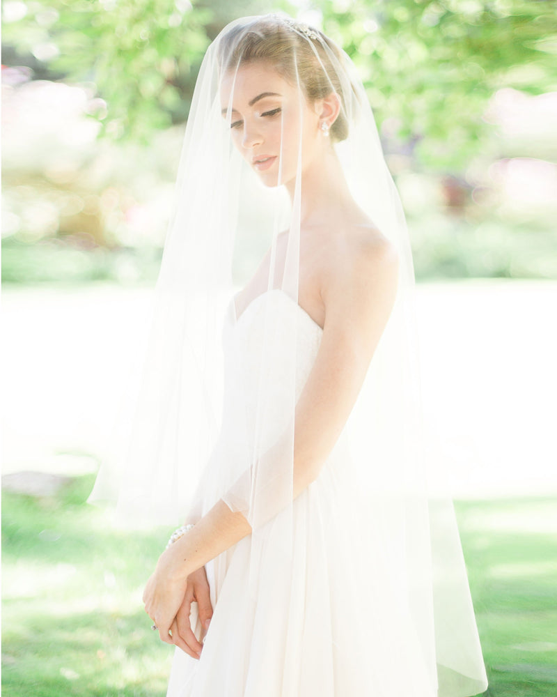 Model wearing circular cut fingertip bridal veil without gathers