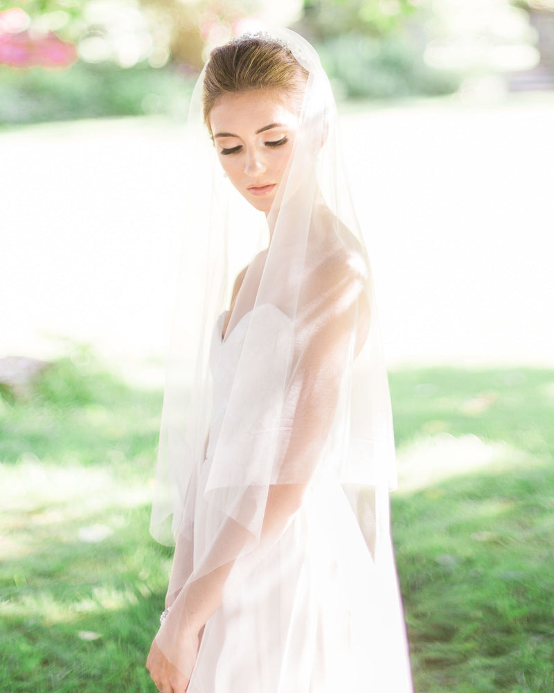 Model wearing circular cut fingertip wedding veil without gathers