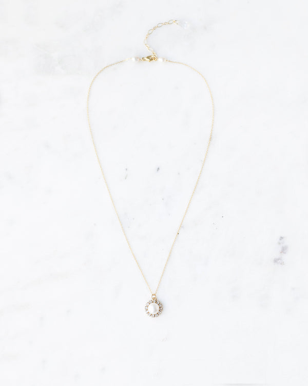 Flat lay photo of our delicate bridal necklace with a pearl drop surrounded by a halo of Swarovski crystals